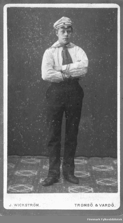 Portrett av ukjent mann. På bildet er han kledt i mørk bukse og en hvit skjorte. Det ligner på en matrosdrakt. På kraven og nederst på mansjettene er det striper. På hodet har han en lys lue med skjerm. Han har et slips i halsen