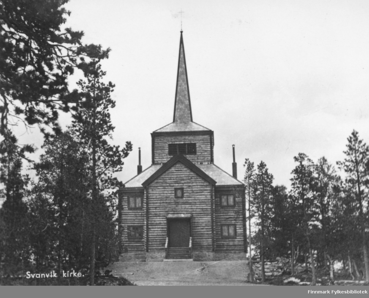 Postkort fra Svanvik Kirke bygd 1932-1934. Kirken er bygd av laftet rundtømmer. Den har et høyt smalt tårnhjelm. Omkring er det furuer