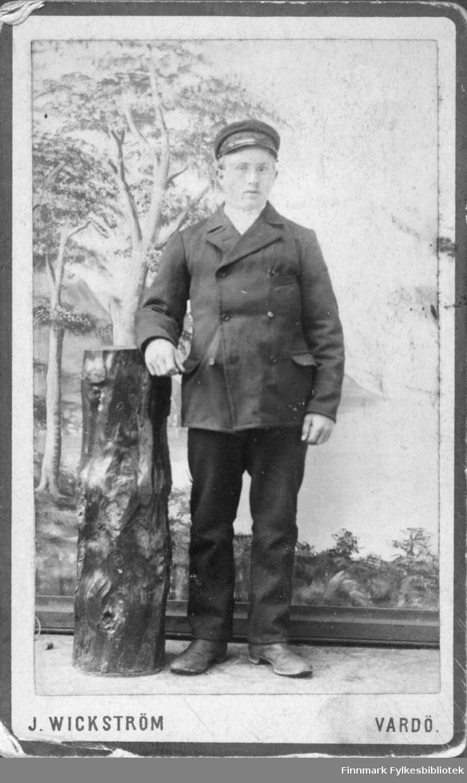 Portrett av en ung menn kledd i en mørk dress med lue. I atelie studio malt bakgrunn hviler hånd på trestubbe  Albumet med bildet kommer fra Ekkerøy, kanskje han kommer derfra.