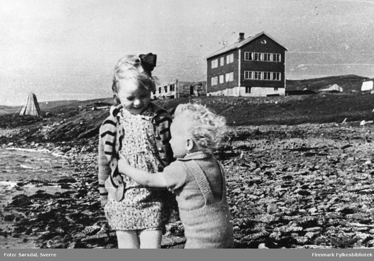 Bildet viser to barn som leker i fjæra i Hamna i Syltefjord. Barna som leker er Randi og Eirik Sørsdal. I bakgrunnen ser man skoleinternatet. Vardø sykehus ble flyttet hit etter bombingen i Vardø under 2. verdenskrig. Ved siden av skoleinternatet bygges det bolig for de ansatte, med materialer fra bombede hus i Vardø. Bildet er tatt høsten 1942.