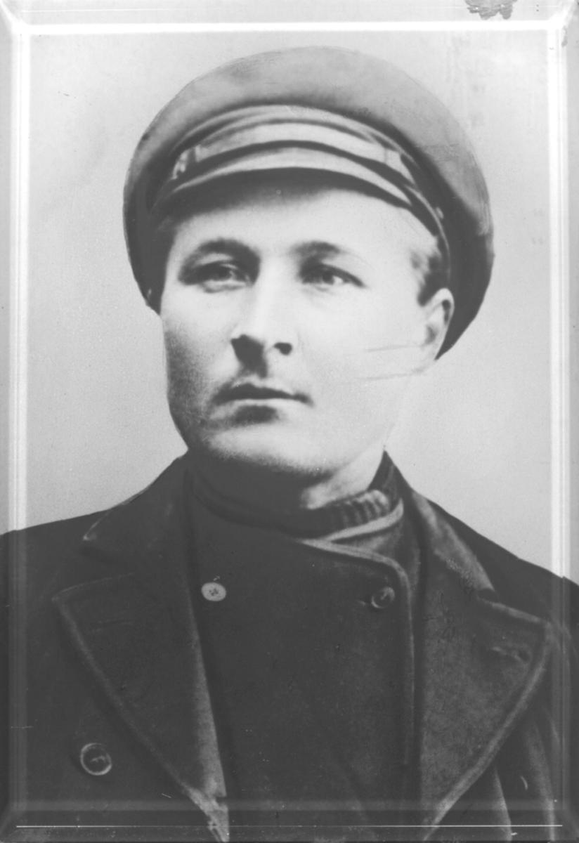 Et portrett av en ukjent mann som er inrammet i en tykk glassplate. Mannen har på seg hatt og jakke.