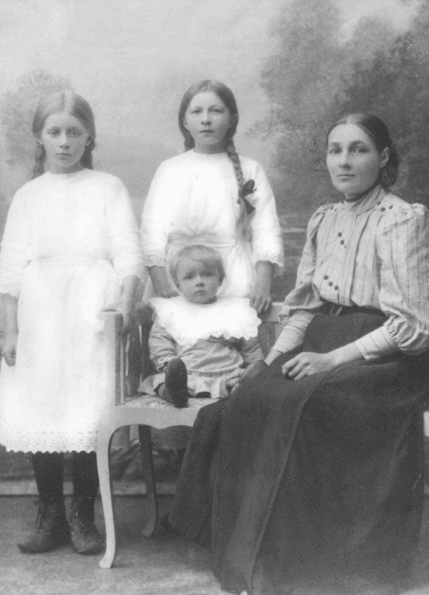 Portrett av ukjente personer. På stolen sitter en kvinne (muligens mor til barna). Hun er kledd i skjorte og skjørt kombinert sammen med et belte. Ved siden av henne sitter en liten gutt med en stor krage. Bak gutten kan man se to jenter i kjoler. Begge har flettet hår. Bildet er trolig tatt på slutten av 1800-talllet.