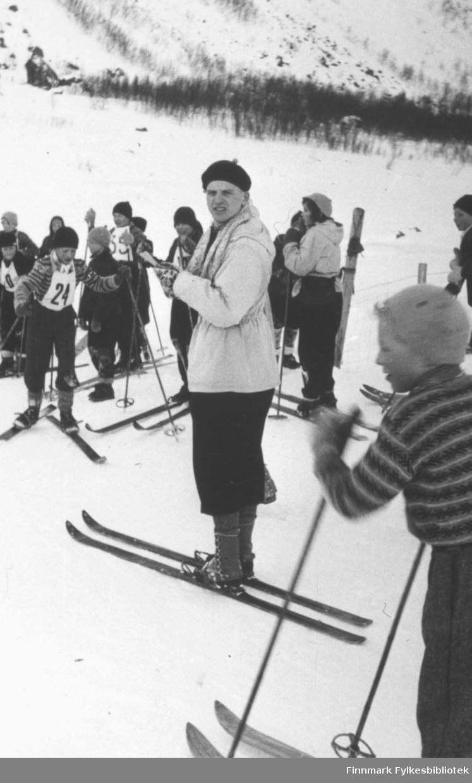 Lærer Jon Martin Alnes omgitt av elever på et skoleskirenn ved Øksfjord barneskole i 1954