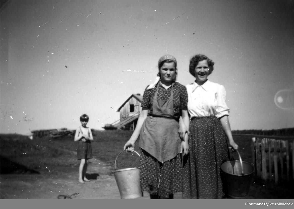 Fotografi av søstrene Anja og Elna Stenbakk. I bakgrunnen står en gutt. Bildet er tatt i forbindelse med fjøsvask. Jentene holder hver sin metallbøtte. Anja har forklæ over kjolen og skaut på hodet. Elna er kledt i en hvit bluse og et mørkt skjørt. Til høyre er det en del av et gjerde. Låven ses bak søstrene