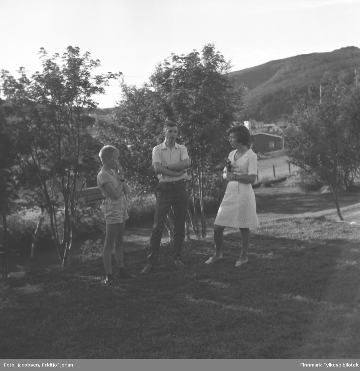 Tre personer står i hagen til Arne Nakken i Rypefjord. De er fra venstre: Sigmund Nakken, Øystein Nakken og Synnøve Nakken. Øystein er far til Sigmund og onkel til Synnøve.