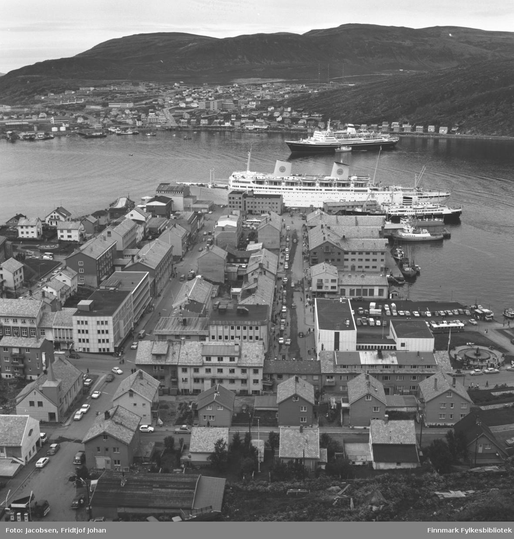 Oversiktsbilde av Hammerfest sentrum med bydelen Fuglenes på andre siden av havna. Vardfjell og Storfjellet ses i bakgrunnen. Bildet er tatt fra fjellet Salen.