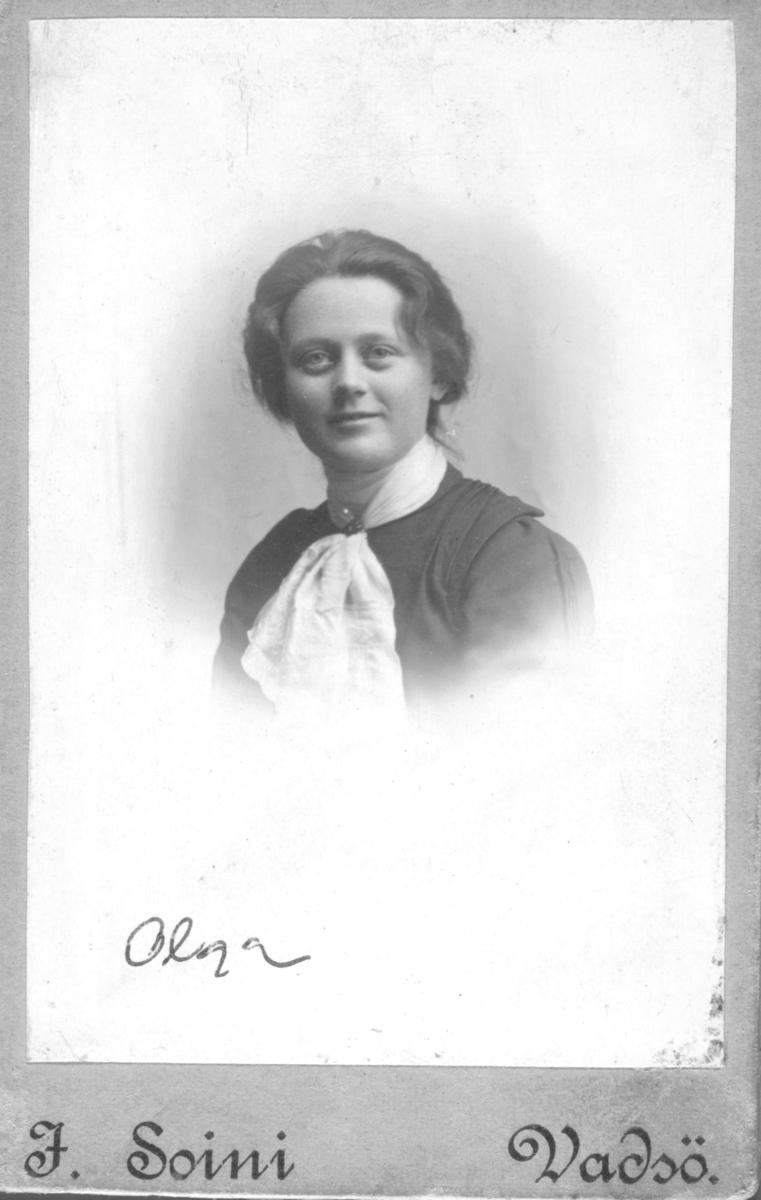 """Portrett av  Olga Marie Persen. Portrettet er tatt av Vadsø-fotograf Jasper Soini i 1902. Registrert som """"Aalga Marie Persen, født 1885 i Vadsø under folketellingen for 1885. Bor på Indrekvænbybaggade 346. På samme adresse bor også hennes far Weksel Persen, født 1852 og  handelsmand og hennes mor,  Evida Persen, født 1863. Weksel Persen er registrert som """"midlertidig tilstedeværende i Kiberg."""" Folketellingen for 1975 i Vadsø prestegjeld har registrert Weksel Persen som Vexel Persen, født 1852 i Vadsø og han er da registrert som handelsbetjent."""