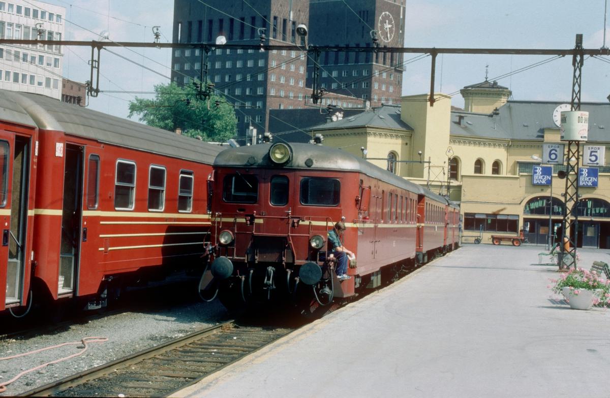 Persontog med elektrisk motorvognsett NSB type 68 på Oslo Vestbanestasjon. Vestbanen. En sporskifter tar en hvil på stigtrinnet.