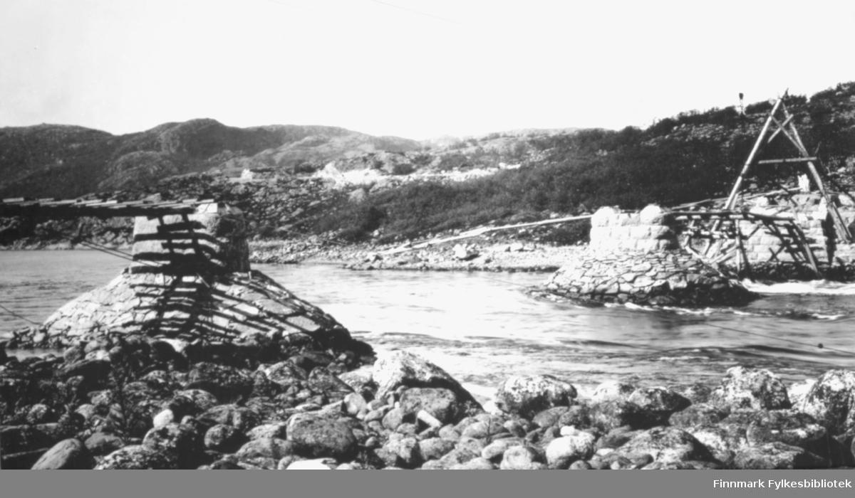 To bro-kar ved Langfjordstrømmen, en på hver side av elven,  sett fra østre bredd. Broa er under bygging. Foto: Chr. B. Heimbeck.