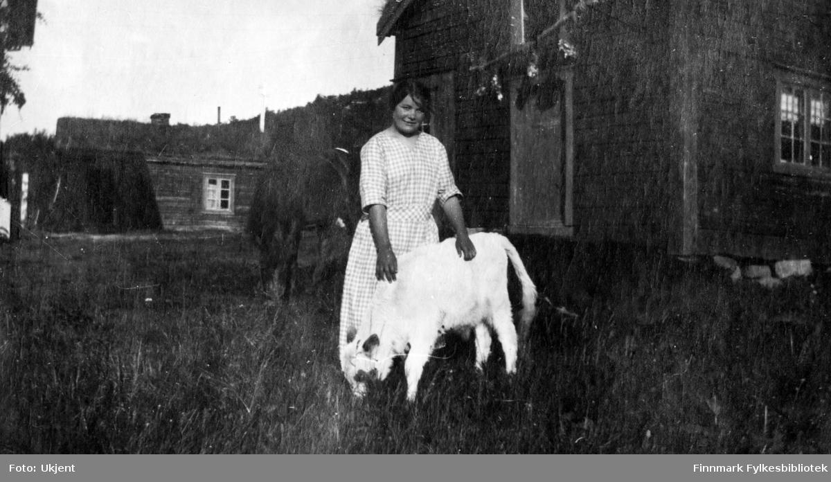 Bildet er tatt fra gården Strømsnes i Jarfjord trolig sommeren 1923. I originalalbumet står det påskrift: 'Klara'. Kvinnen har på seg en kjole og poserer her sammen med en liten kalv. Bak henne kan man se enkelte bygninger med vinduer med gardiner, og dører.