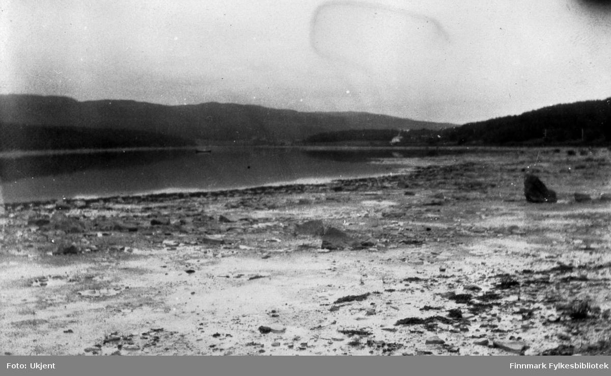 Bildet er tatt av Jarfjordbotn. Huset som skimtes helt til høyre i bildet er gården Stømsnes. I bildet kan man se fjæra, havet , skog og fjell. Ute på vannet kan man se en liten båt. I fjæra kan man se et par store steiner.