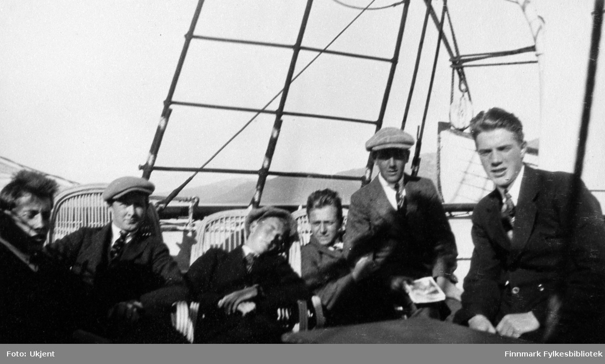 Her poserer en gruppe med gutter ombord et skip som trolig er Hurtigruten. Alle guttene er ukjente. De fleste av dem sitter på stråstoler. Tre av guttene har på seg luer, nummer fem fra venstre holder et magasin eller en bok i hånden. Guttene har på seg slips, jakke og bukser. Bak dem til høyre kan man se en livbåt og bak livbåten kan man se fjell.