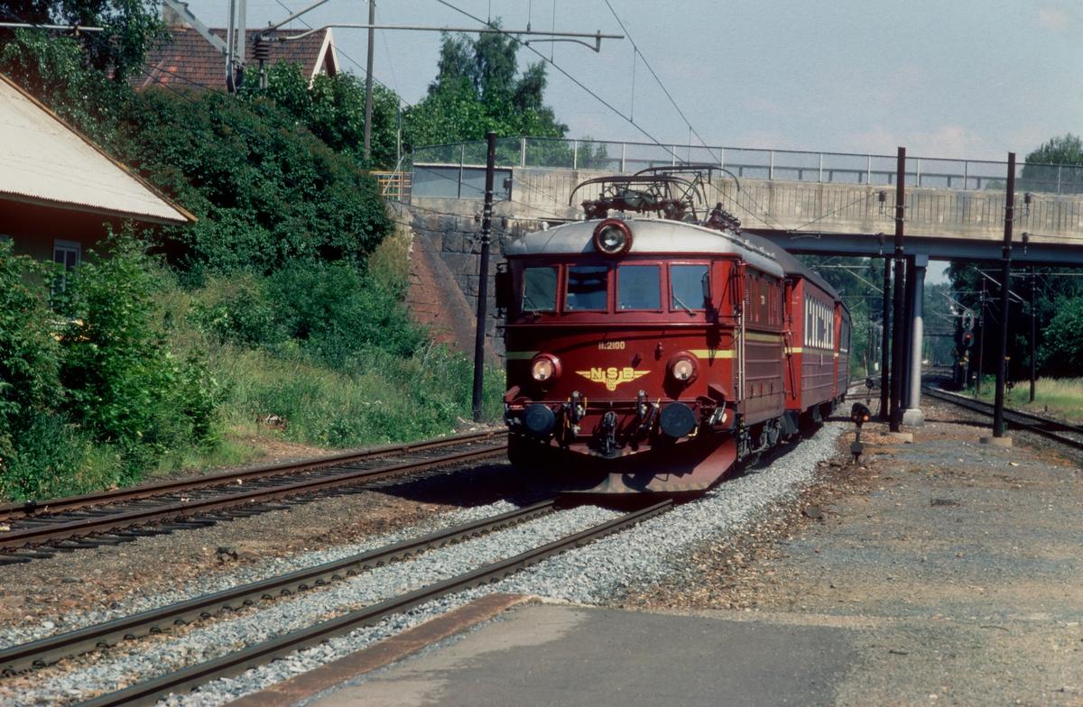 Persontog med NSB elektrisk lokomotiv El 11 2100 passerer Stabekk stasjon på Drammenbanen.