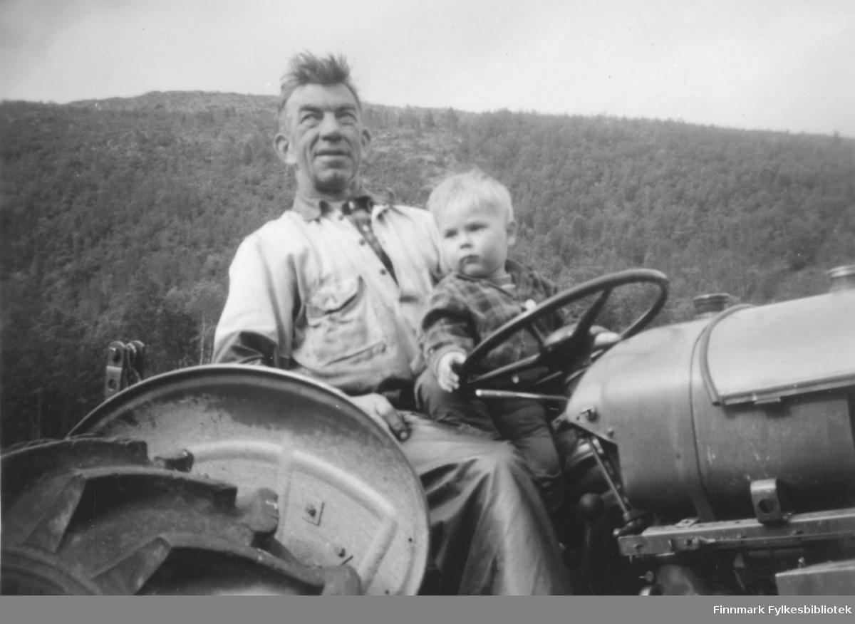 Kristian Wisløff pløyer jorda for en familie i Alta. Her ser vi han sittende på en David Brown-traktor med en liten gutt på fanget. I bakgrunnen ser vi en skogskledd høyde i terrenget