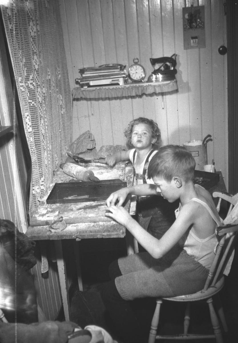 Julebakst under krigen i Nyborgveien i Vadsø. Guttene er Øystein og Tor Hauge(nærmest kamera).