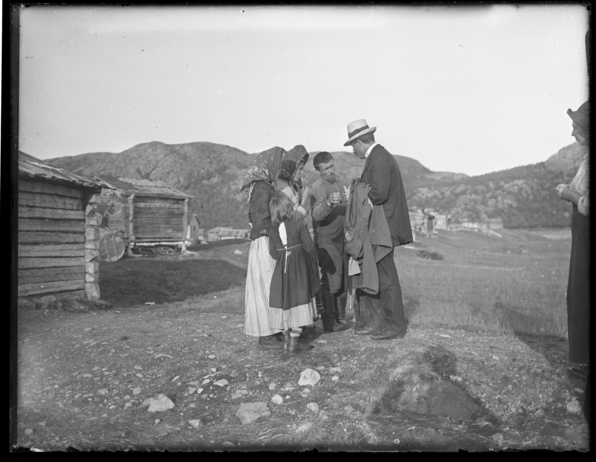 Ved skoltebyen i Boris Gleb. To kvinner, ei jente og en mann, alle skoltesamer, og står og prater Johan O. A. Grasmo. Kvinnene er kledt i skjørt og russiske sjal. Mannen har høye støvler. I bakgrunnen er det hus bygd av lafta tømmer. Kona Anne Marie Grasmo i høyre billedkant.