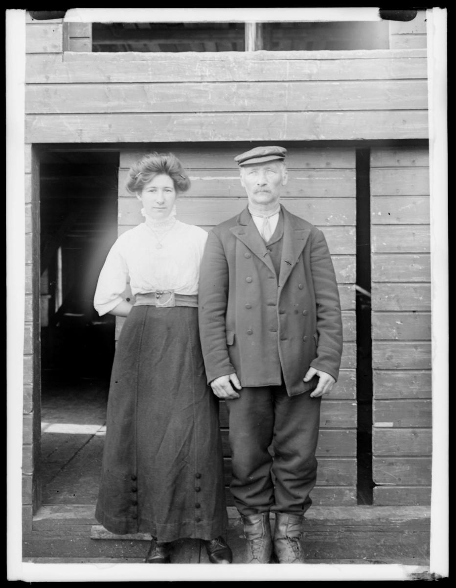 Portretter fra Makkaur. En ung kvinne og en eldre mann. Kvinnen, som er på flere bilder, har oppsatt hår og er kledt i hvit bluse, belte og svart skjørt. Mannen har caps, jakke, bukse og ankelhøye sko.