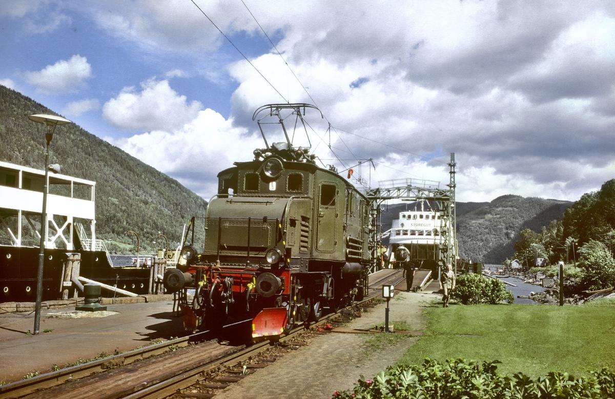 Rjukanbanen, Norsk Hydro. Elektrisk lokomotiv RjB 14 (NSB El 1 2001) på fergeleiet ved Mæl. Jernbanefergen M/F Storegut har lagt til kai og vognene skal skiftes av fergen med skiftetau. Til venstre D/F Ammonia.
