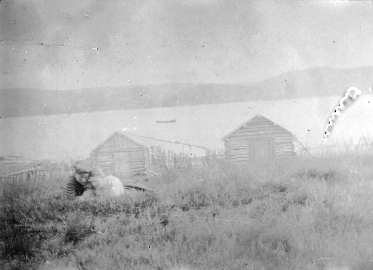 En dame og mann ligger i gresset og ser opp på fotografen. Lenger ned i bakken er det to sku eller båthus. På vannet ligger en liten båt.