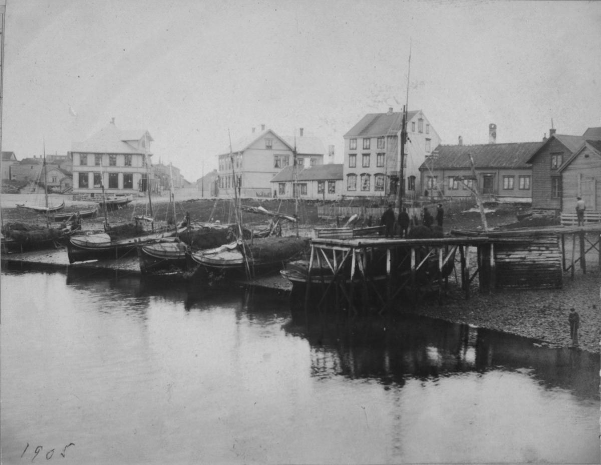 Flere menn står på ei kai. I fjæra ligger det båter. Bygninger i bakgrunnen.