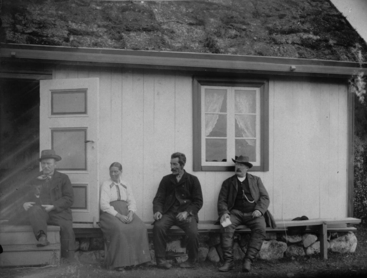Fossestuen 18. august 1907. Ferdig i 1907. I 1979 tok flommen hytta. Elen Hesenget, Ingebrigt Hesenget og baker Karl Oluf Olsen sitter på en benk foran hytta. På trappa sitter Viktor Olsen, Vardø.