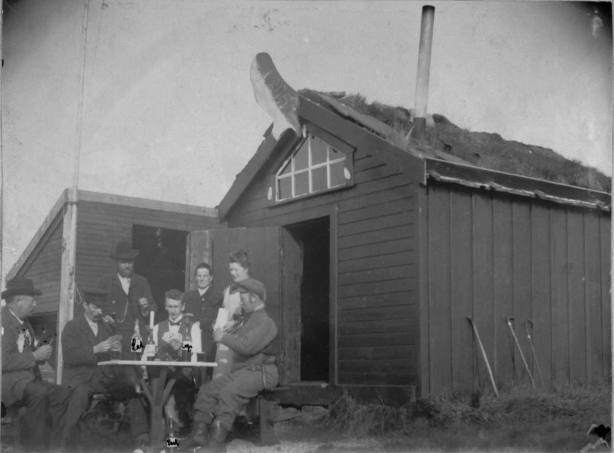 Søndagsarbeid. Mennene sitter rundt bordet utenfor hytta . Flasker står på bordet.