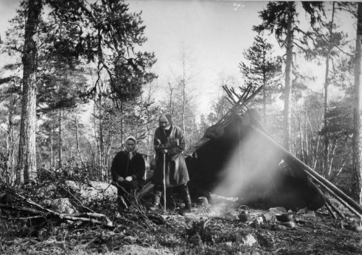 En ung kvinne og en eldre mann utenfor en lavvo, omgitt av furuskog. Det røyker fra et leirbål og kaffekjel og kokekar står klare på bakken foran teltet