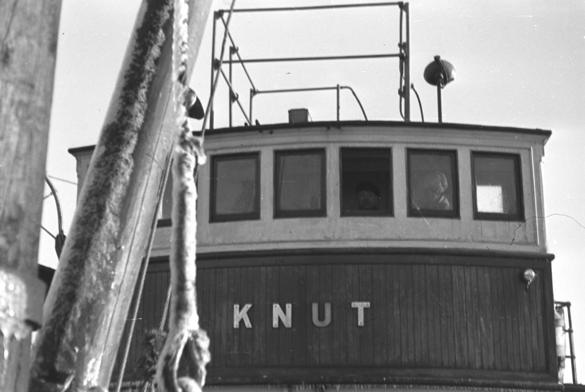 """Rorhuset på skøyta """"Knut"""" som også ble brukt som lokalbåt. Stedet og mannen i rorhusvinduet er utkjent."""