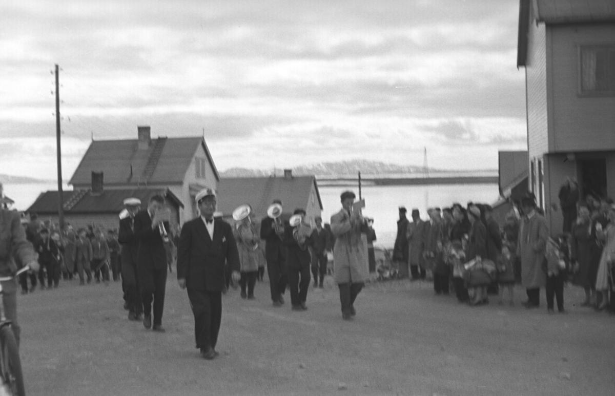 17. mai-tog i Joki-svingen i ytrebyen i Vadsø. Fremst i toget går Olaf L. Holmen med korpset like bak.