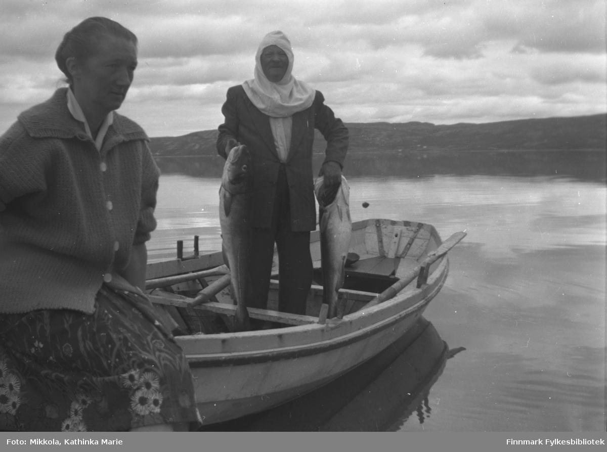 Etter fisketur på fjorden ved Mikkelsnes. Marine Smuk sitter på ripa i baugen av båten. Aksel Mikkola med mygghette har fått to digre torsk. Bildet er tatt ved samme anledning som 05007-202, 05007-203 og 05007-297
