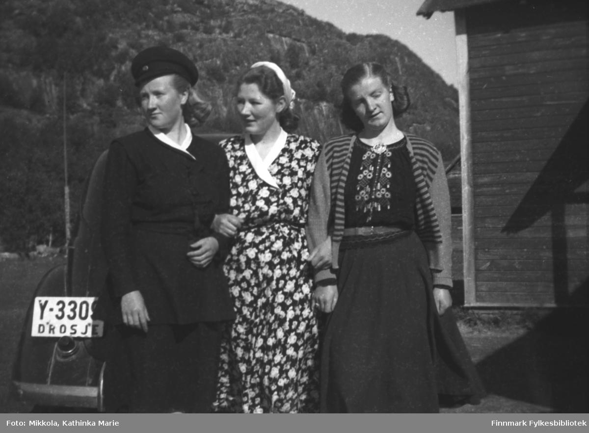 Tre av Mikkola-søstrene foran Karl Arvolas drosje (Y-3309?) utenfor Mikkelsnes. Fra venstre: Herlaug, Kari og Astrid. Herlaug har uniformslue, kanskje sjåførens?