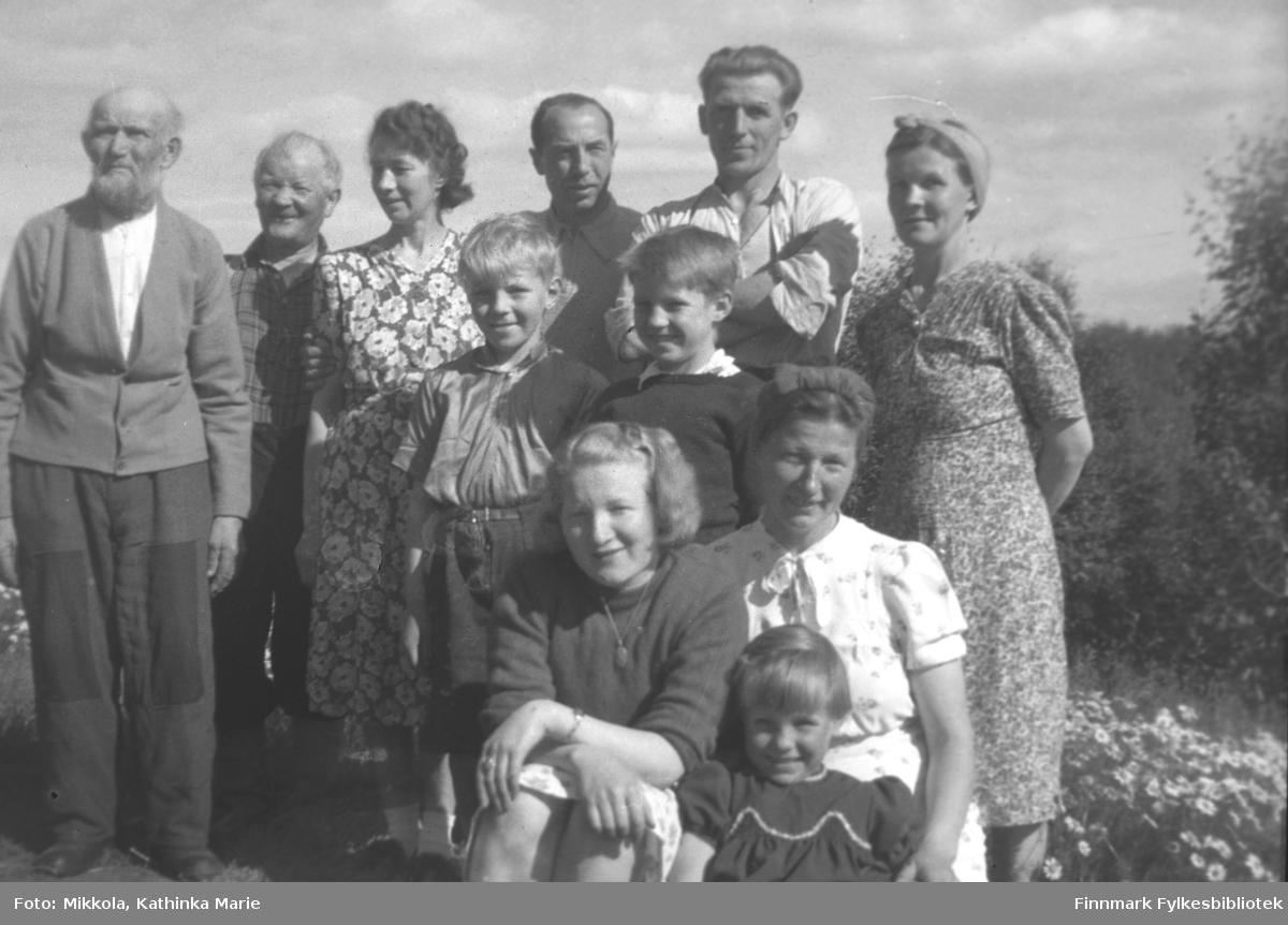 Mange medlemmer av Mikkola-familien samlet til fotografering. Øverst fra venstre: Isak Sirkka Mikkelsen, Aksel Konrad Mikkola, Hilja Sirkka Mikkelsen, ukjent mann som kan være en finlender, Arne Mikkelsen, Jenny Sirkka Mikkelsen. Foran: To ukjente gutter, Gudrun Mikkola, Klara Mikkelsen. Helt foran ei ukjent jente