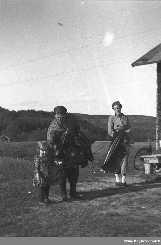 Kathinka Mikkola med reiseveske leier en ukjent småjente. Til høyre i bildet Gudrun Luneborg med regnfrakk over armen