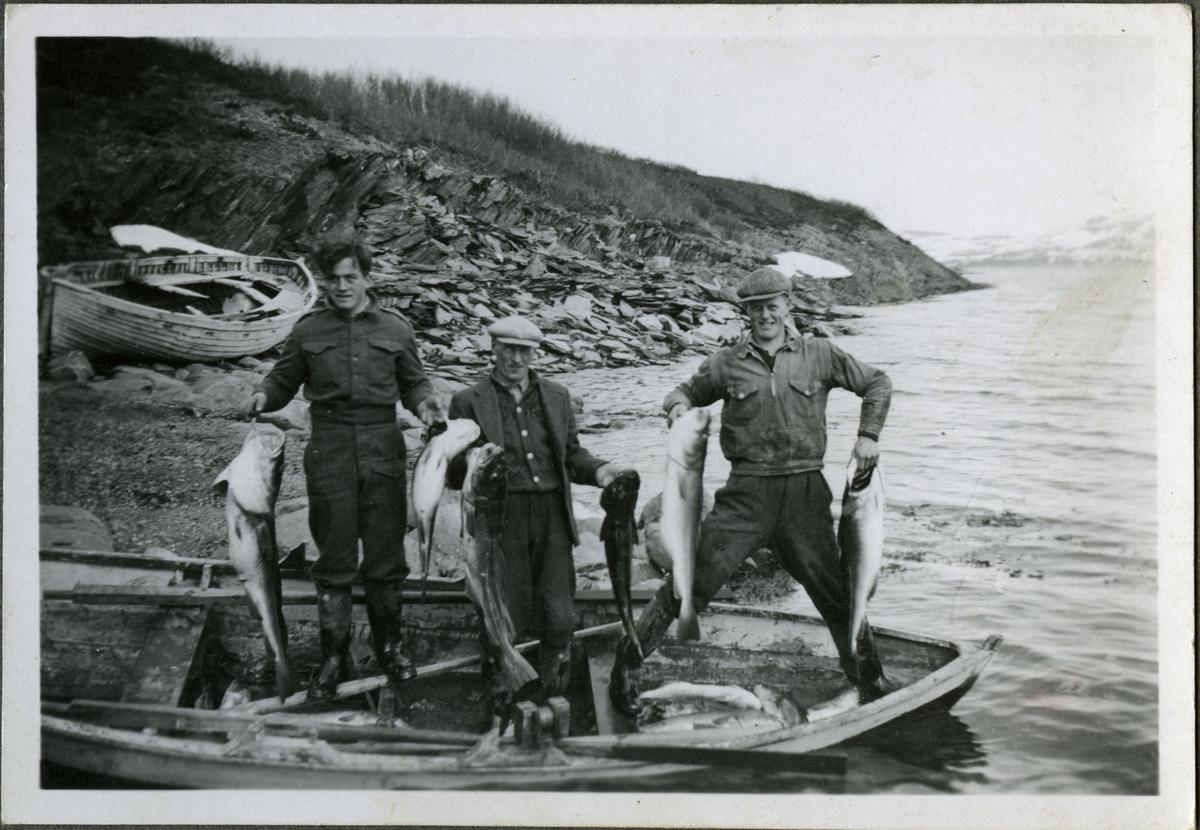 Ukjente menn viser fram fangsten. Det ligger flere fisk på bunnen av båten. Årene ligger langs sidene på båten. Mennene er kledd i jakker bukser, støvler og luer. De er trolig tilknyttet (muligens arbeidere på) skiferbruddet i Friarfjord.I bakgrunnen kan man se skiferstein langs vannkanten.