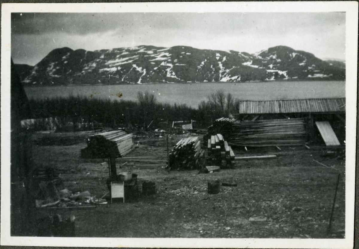 Konstruksjon av bygninger på skiferbruddet i Friarfjord. Byggematerialet er blitt stablet opp. Bak haugene med trematerialet ble det senere bygget en kantine for arbeiderne på skiferbruddet. I forgrunnen kan man se noe som ligner en ved ovn med en stol foran. I bakgrunnen kan man se havet og fjell.
