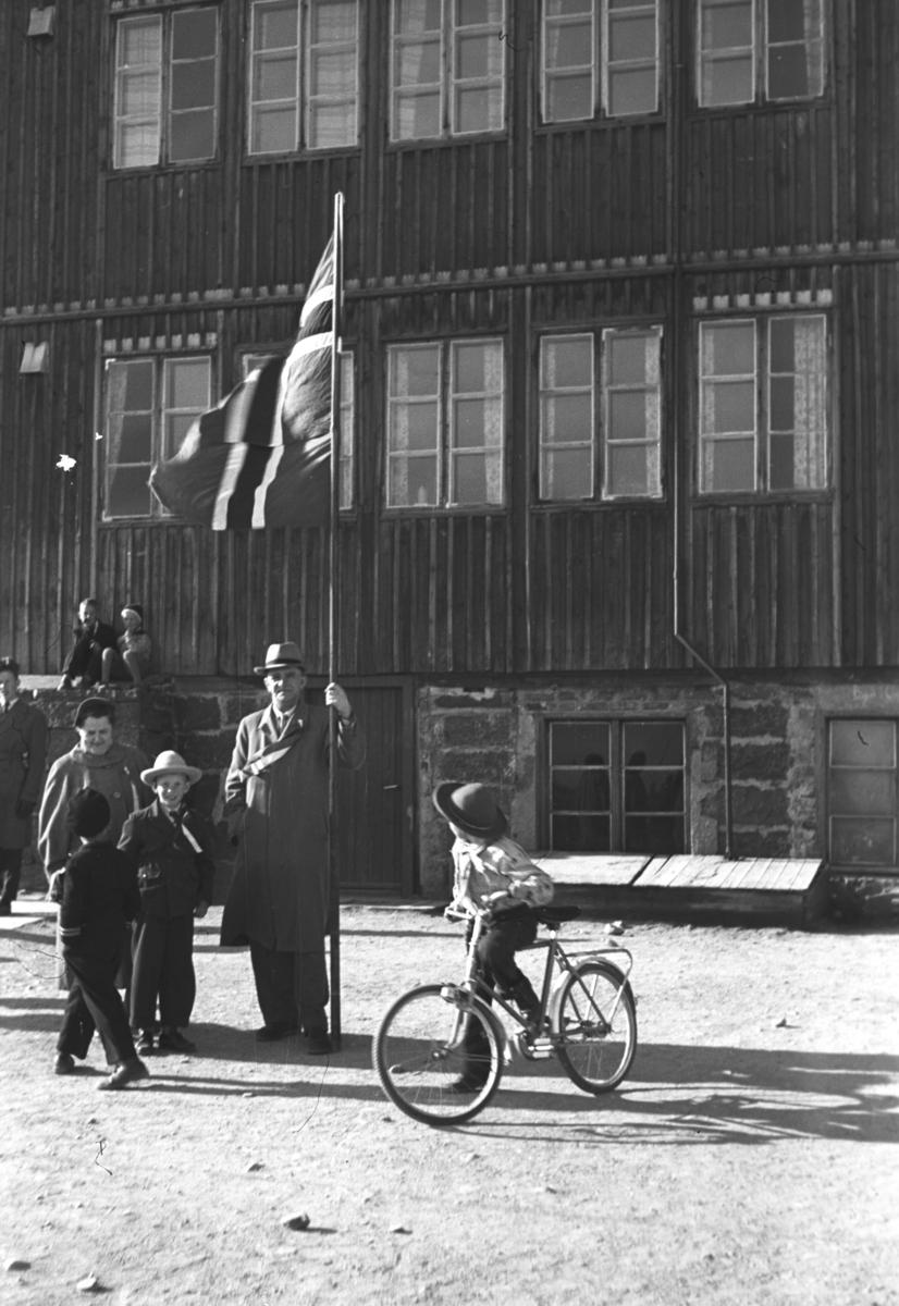 Leif Hauge står utenfor skolen i Vadsø med et stort flagg i hånda. Han er formann i 17. mai-komiteen. De andre på bildet er ukjent.