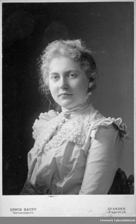 Portrett av en dame i en ganske lys bluse med volanger. En brosje er festet øverst i kragen. Portrettet er tatt hos Hulda Bentzen i Bergen.