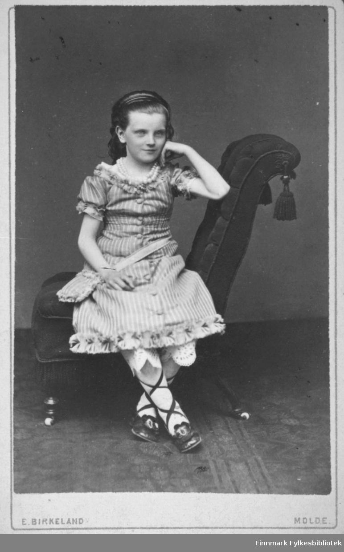 Portrett av en ung jente som sitter i en stol. Hun har en stripet kortermet kjole, lyse strømper og mørke sko med reimer oppover leggene. Et perlekjede henger rundt halsen hennes. Portrettet er tatt hos E. Birkeland atelier i Molde.