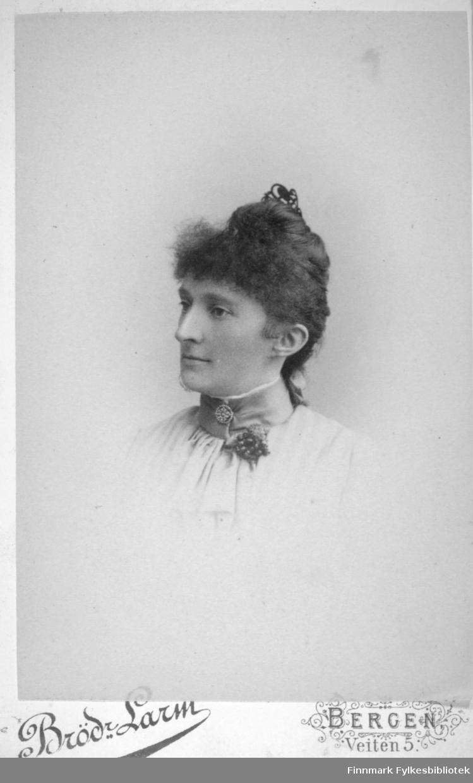 Portrett av en dame i hvit bluse. Hun har håret knytt sammen med et hårbånd på toppen av hodet. Hun har et pyntebånd rundt halsen. Det har en brosje og noe som ser ut som en liten blomsterpynt. Portrettet er tatt av Brødrene Larm i Bergen i februar 1889
