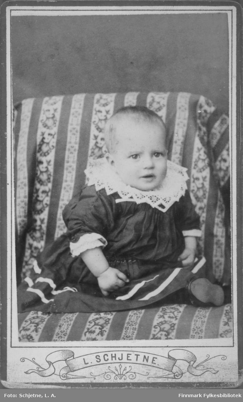 Et lite barn fotografert sittende i en stol med stripet/mønstret trekk. Barnet har en mørk kjole med to hvite striper nede og en bred heklet krage. En sko stikker fram fra kjolen nede til høyre på bildet.