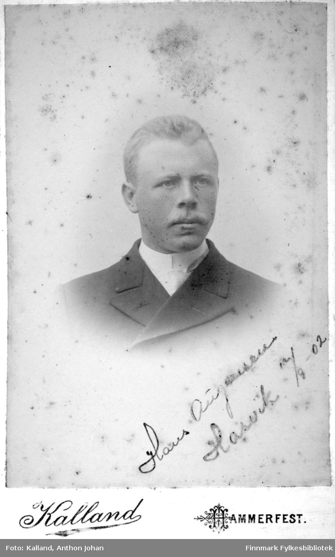 Portrett av Hans Augensen. Han har en mørk dressjakke og hvit skjorte eller genser på seg.