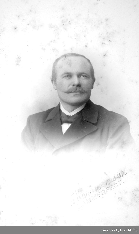 Portrett av en mann iført en mørk dressjakke, hvit skjorte og sløyfe i halsen.