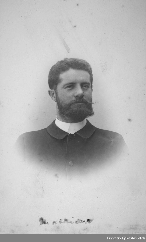 Portrett av en mann iført mørk dressjakke. I halsen ses litt av den hvite kragen.