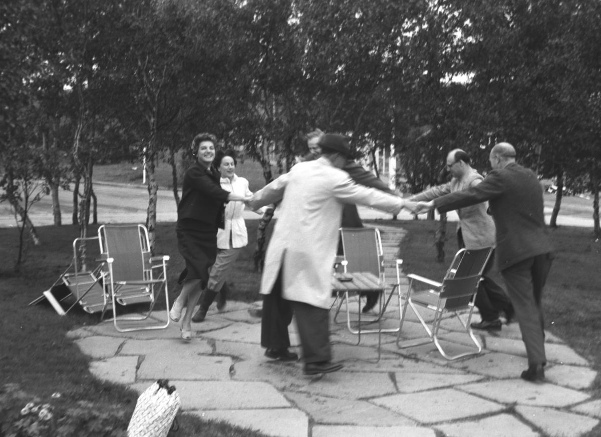 Noen menn og kvinner danser rundt et bord og noen stoler. Personer og sted er ukjent.