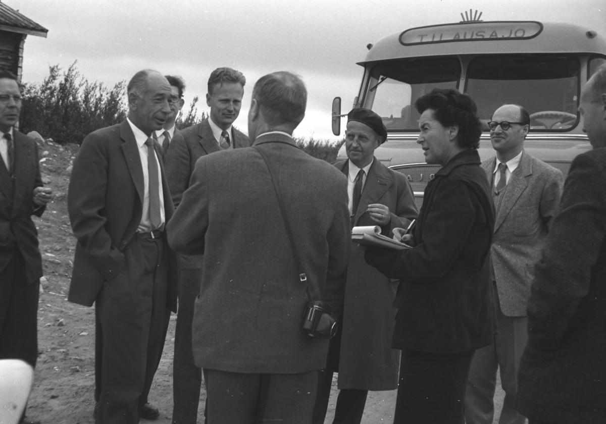 """En liten folkemengde står foran en parkert buss. Bussen på bildet er antakelig finsk. På grillen skimtes bokstavene """"AJO"""". Det kan være den tidligere finske bussprodusenten AJOKKI. Ajokki busser ble produsert i Tammerfors i perioden 1942-1989. Personer og sted er ukjent."""