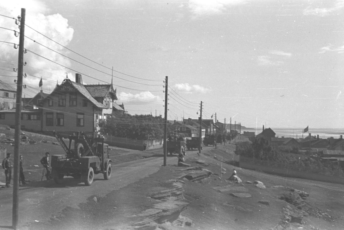 En kolonne med lastebiler og anleggsmaskiner kjører nedover en gate i Vadsø.