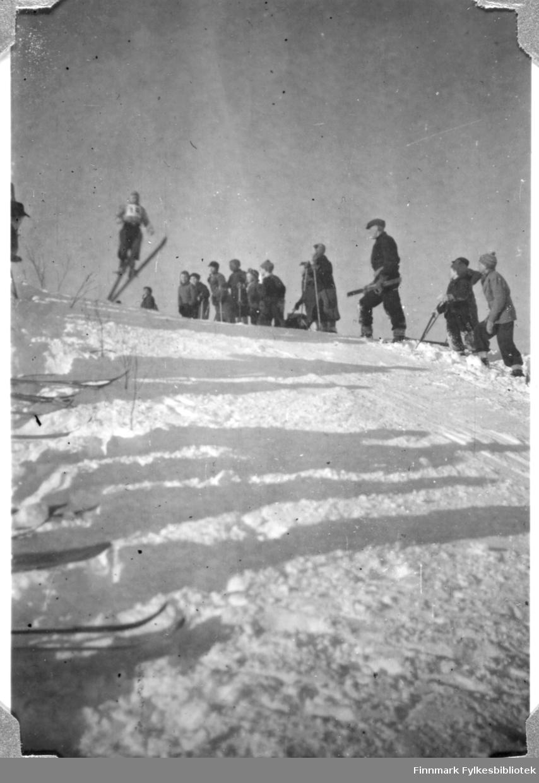 Hopprenn i Fossen i 1946. Roald Wara i svevet. Roald var sønn av vaktmester Wara på folkeskolen. Erling Mæggilæ er klar for å måle lengden på hoppet.