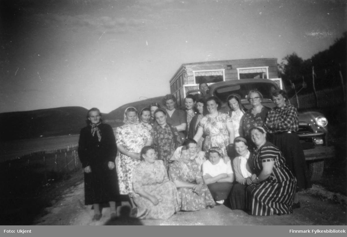 Nesseby husmorslag er ute å reiser. Her poserer de foran en lastebil Chevrolet 1954 med campingvogn. Kvinnene har på seg kjoler, skjørt og skjorter. Enkelte har på seg skaut, andre har briller. På campingvognen kan man se et par vindu med gardiner i. De står parkert på kanten av en vei. I bakgrunnen kan man se fjell.