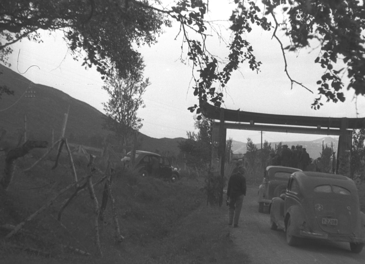 To biler kjører under en slags portal på en skogsvei og et par personer går ved siden av. Personer og sted er ukjent.