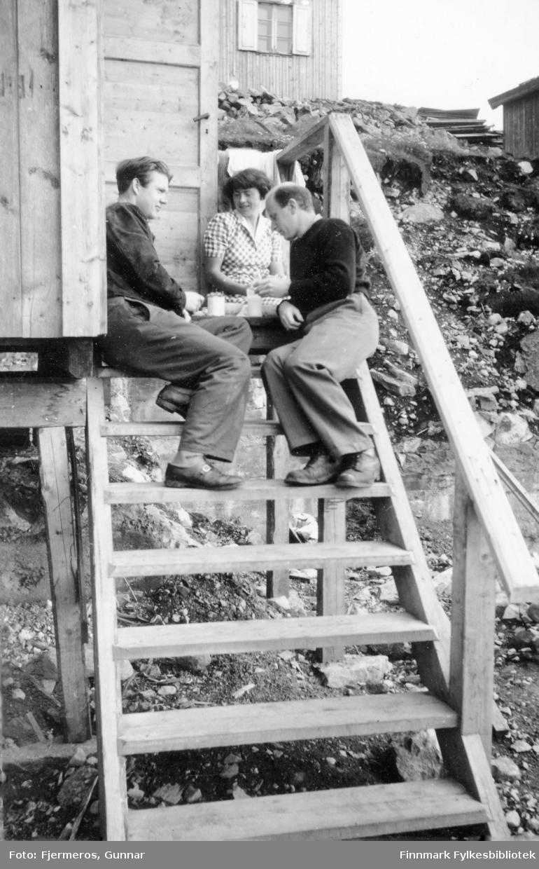 Tre personer sitter på en trapp til et gjenreisningshus en sommerdag. Personene er ukjente.